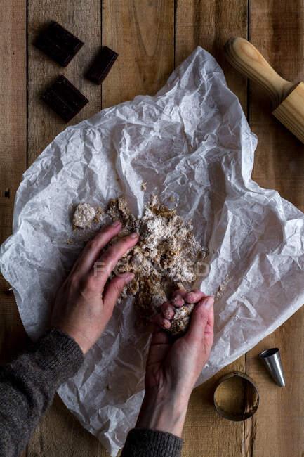 Вище врожай тримає шоколадне тісто в руці над білим випіканням паперових шоколадних металевих форм печива і валяння шпильки на дерев
