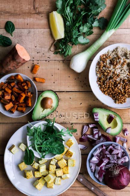 De l'oignon coupé ci-dessus et l'avocat avec la patate douce et les légumes verts dans le processus de préparation des repas sur la table rustique — Photo de stock