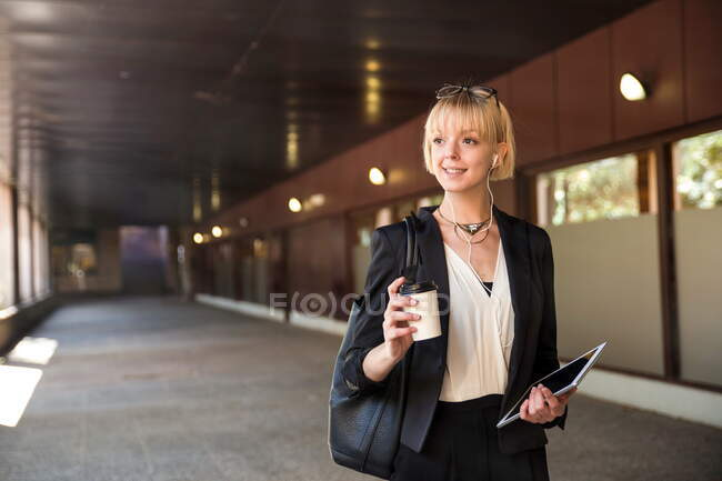 Cheerful businesswoman with paper cup and tablet — Stock Photo