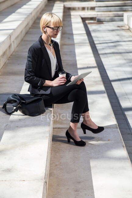 Pretty businesswoman with tablet on steps — Stock Photo