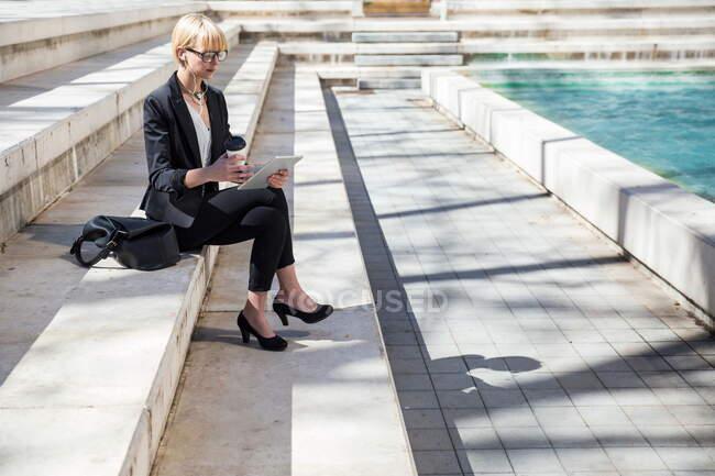 Бічний вид блондинки ділова жінка сидить на сходах і використовує планшет у міському ставку. — стокове фото