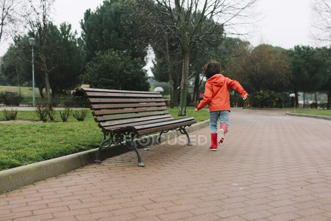 Back view of anonymous adorable joyful child in red raincoat and rubber boots having fun running on street in park in gray day — Stock Photo