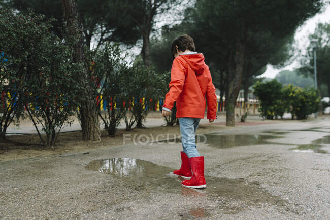 Rückansicht eines anonymen liebenswerten fröhlichen Kindes in rotem Regenmantel und Gummistiefeln, das an grauen Tagen auf der Straße im Park mit einer Pfütze spielt — Stockfoto