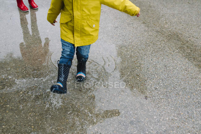Cropped unrecognizable adorable joyful children in red and yellow raincoat and rubber boots having fun playing in puddle in street in park in gray day — Stock Photo