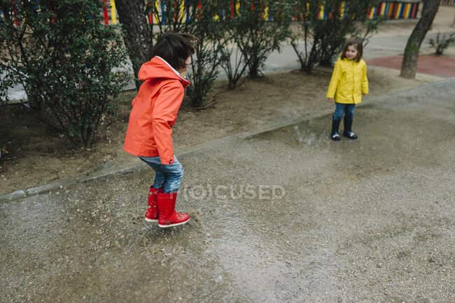 Entzückende fröhliche Kinder in rotem und gelbem Regenmantel und Gummistiefeln, die an grauen Tagen in einer Pfütze auf der Straße im Park spielen — Stockfoto