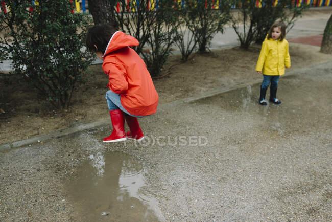 Приємні радісні діти в червоному і жовтому плащі і гумові чоботи весело бавляться в калюжі на вулиці в парку в сірий день. — стокове фото