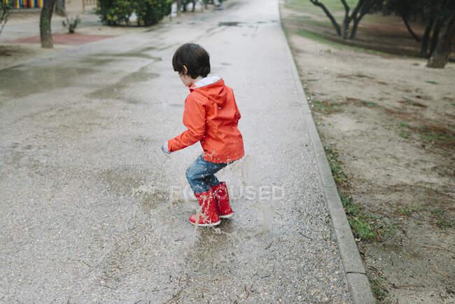 На задньому плані невідоме чарівне радісне дитя в червоному плащі і гумові чоботи весело бавляться з калюжею на вулиці в парку в сірий день. — стокове фото