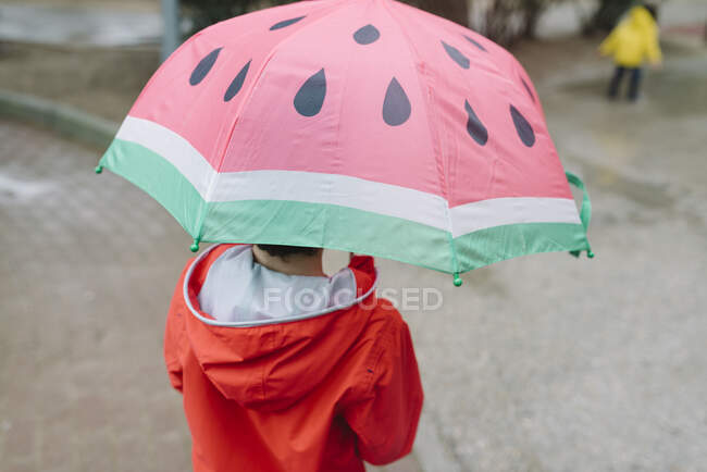 Back view of unrecognizable kid with watermelon styles open umbrella in red raincoat and rubber boots walking in park alley in gray day — Stock Photo