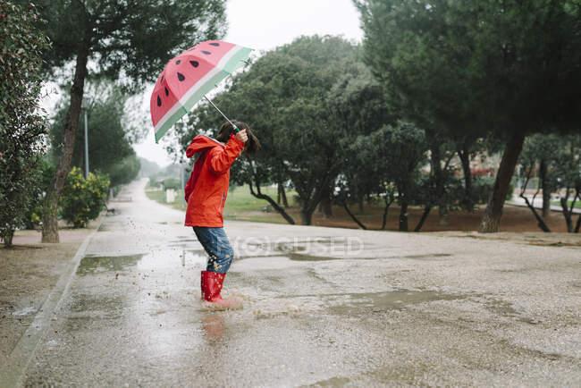 Бічний вид активного малюка з відкритою парасолькою в червоному дощовику і гумові чоботи стрибають в парку алеї в сірий день — стокове фото