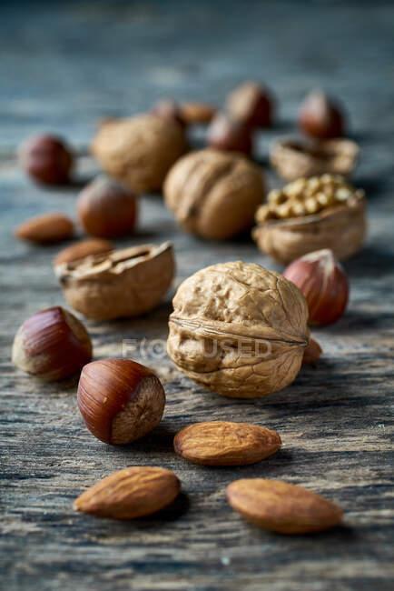 Коричневые спелые орехи и грецкие орехи на столе — стоковое фото