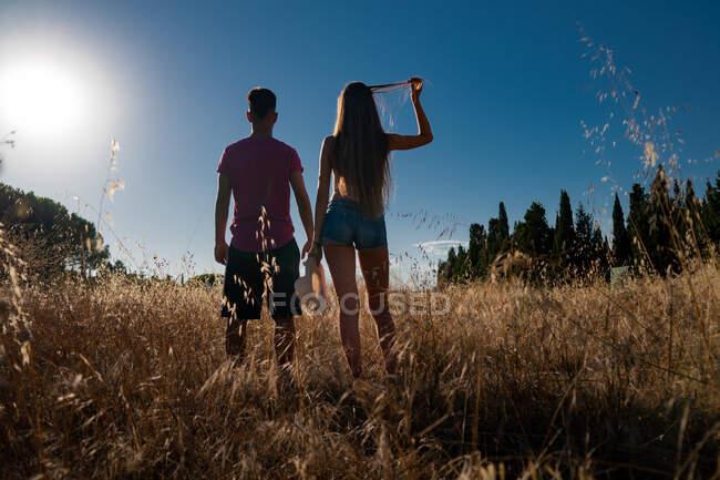 Giocoso giovane maschio in piedi con femmina in campo con cappello in mano — Foto stock