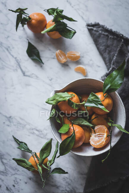 Апельсиновые танжерины в керамической чаше на мраморном столе — стоковое фото
