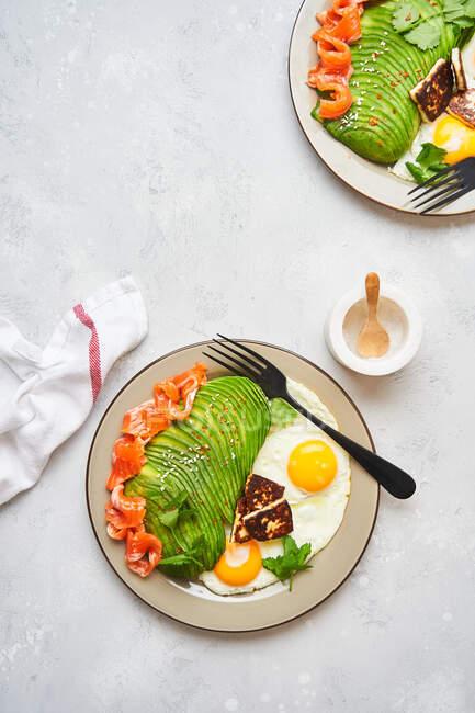 Здоровый завтрак с жареными яйцами и авокадо — стоковое фото