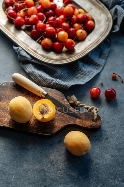 Colocação plana de deliciosos pêssegos cereja e amarelo servido no prato em um fundo rústico — Fotografia de Stock