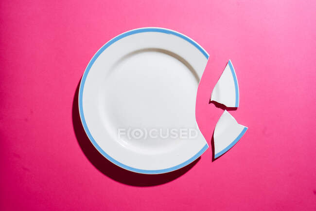 Top view of broken clean white plate with blue border and shards on gradient pink background — Stock Photo