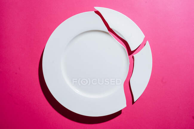Broken white plate on pink background — Stock Photo