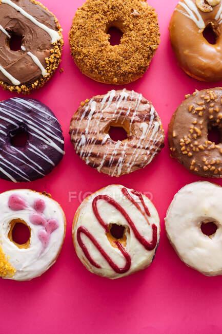 Variedade de donuts no fundo rosa — Fotografia de Stock