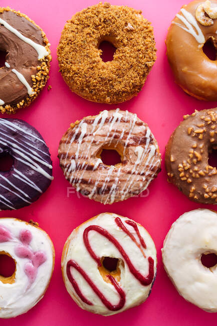 Variety of doughnuts on pink background — Stock Photo