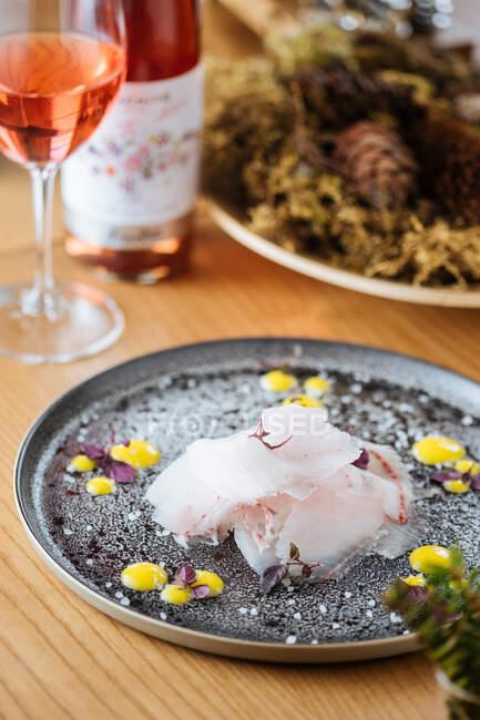 Stroganina o carpaccio hecho con pescado blanco fresco en rodajas servido en plato de plata decorado con salsa y copos de sal en mesa de madera con vino de rosas y plato en el fondo - foto de stock