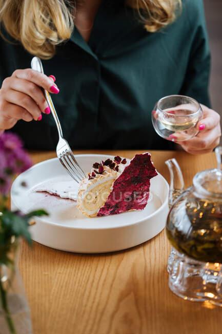 Обрезание женщины в темно-зеленой блузке сидя за деревянным столом едят вкусный торт с красными ягодами подается в белой керамической тарелке и пить травяной чай — стоковое фото