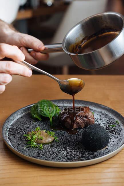 Cortado persona anónima manos verter salsa en delicioso bistec de carne gourmet con salsa y hierbas servidas en plato de plata de metal - foto de stock