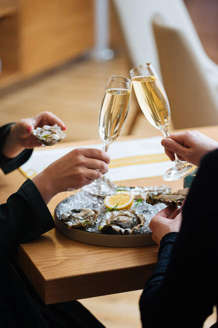 Unrecognizable couple with glasses of champagne trying delicious oysters with lemon and herbs in restaurant — Stock Photo