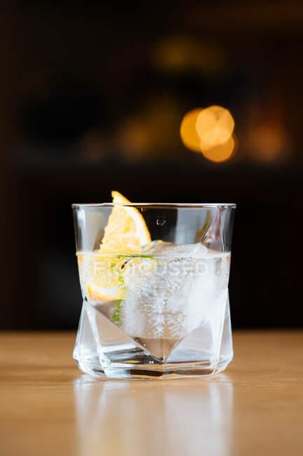 Copa con cóctel alcohólico frío con limón y cubitos de hielo colocados sobre la mesa sobre fondo negro - foto de stock