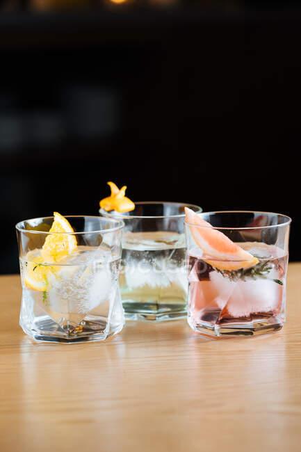 Copas de vidrio con cócteles alcohólicos fríos con varios cítricos colocados sobre la mesa sobre fondo negro - foto de stock