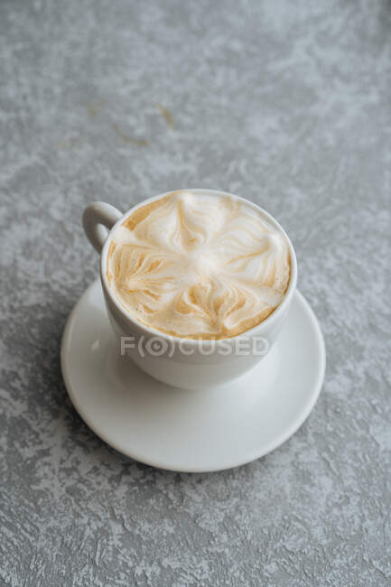 Top view of cup of hot cappuccino with latte art served on white saucer on light grey textured background — Stock Photo