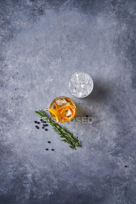 From above top view of glass cup with cold old fashioned cocktail with whiskey and orange peel placed on grey table with rosemary plant a pepper grains — Stock Photo