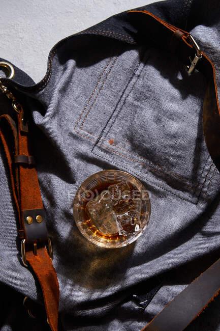 Верхній вид скляної чашки віскі з льодом поміщений на денімському одязі в барі — стокове фото
