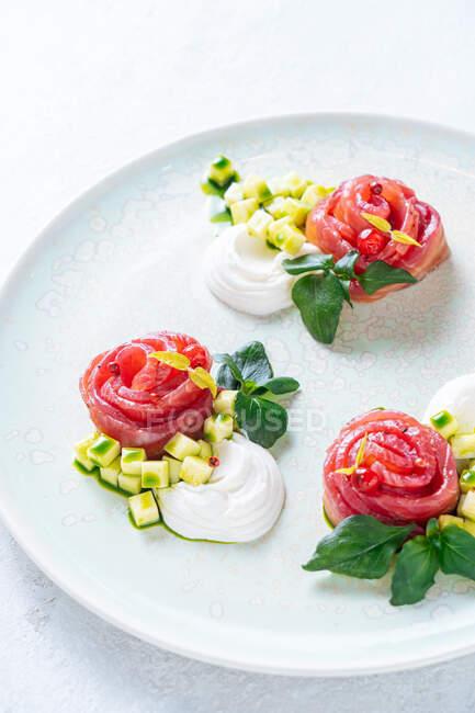 Rollos de salmón con cebolla y hierbas servidas en plato de cerámica blanca sobre fondo de mesa blanco - foto de stock