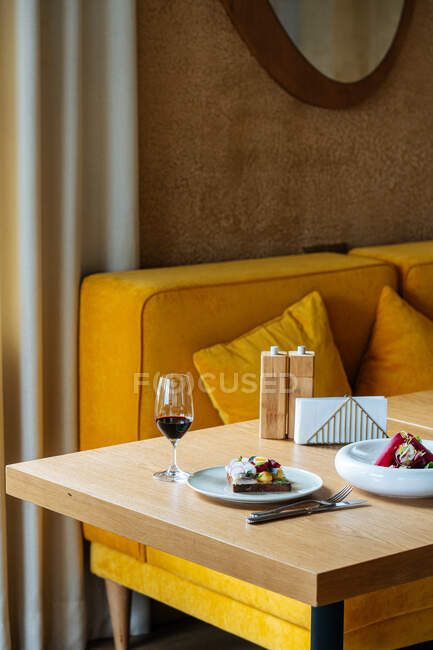 Exquisite dishes and glass of red wine placed on table during dinner in luxury cafe — Stock Photo