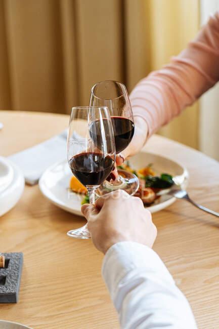 Casal cortado irreconhecível clinking copos de vinho tinto e propondo brinde durante o almoço em restaurante de luxo — Fotografia de Stock