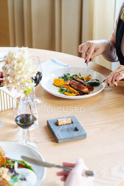 Неузнаваемый обрезанный человек ест и пьет красное вино в роскошном ресторане — стоковое фото