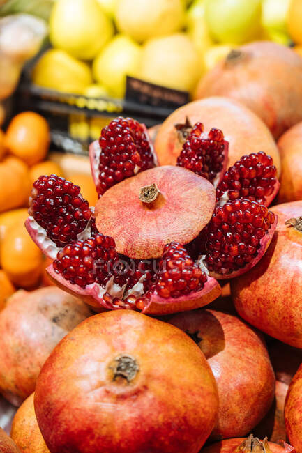Cute fresh pomegranate placed on heap of fruits on stall in grocery store — Stock Photo