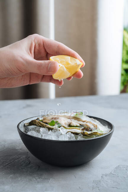 Unrecognizable cropped person squeezing lemon on delicious oysters on Ice cuber on a bowl in restaurant — Stock Photo