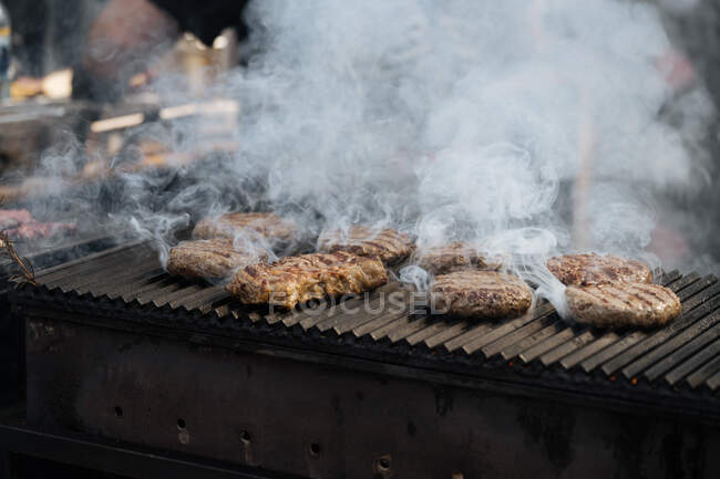 From above of cooking cutlet with smoke on grill in market stall — Stock Photo