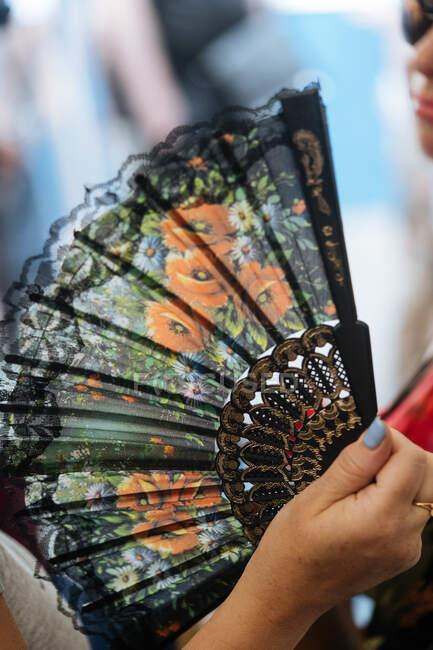 Леді з кольоровим вентилятором з квітами в руці в ринковій кабінці — стокове фото