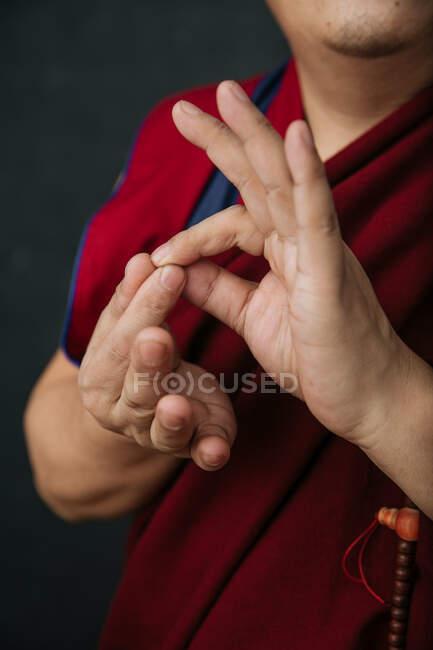 Закрытие рук урожая молящегося тибетского монаха в традиционном красном халате с мудрой символической рукой жестом — стоковое фото