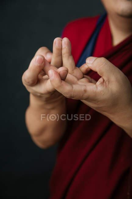 Primo piano delle mani del raccolto pregando monaco tibetano in tradizionale veste rossa con mudra gesto simbolico mani — Foto stock