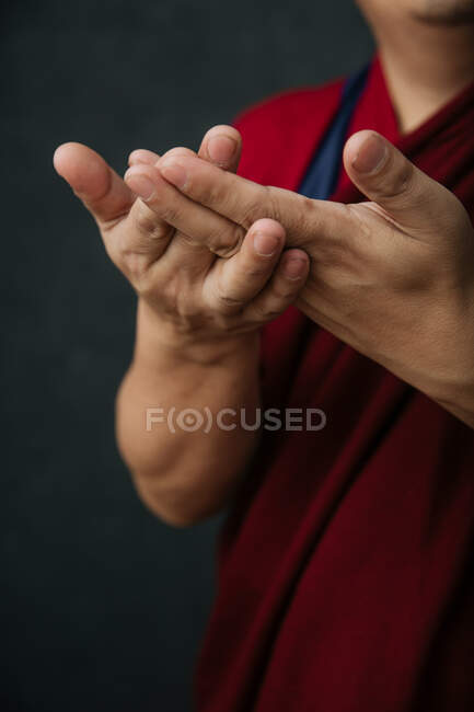 Closeup of hands of crop praying Tibetan monk in traditional red robe with mudra symbolic hands gesture — Stock Photo