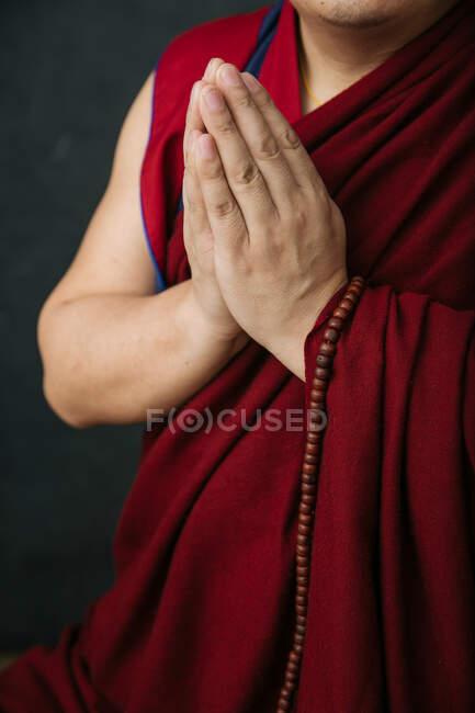 У традиційному червоному халаті хрестився тибетський монах з намистинами та руками, складеними в мудрі Намасте. — стокове фото