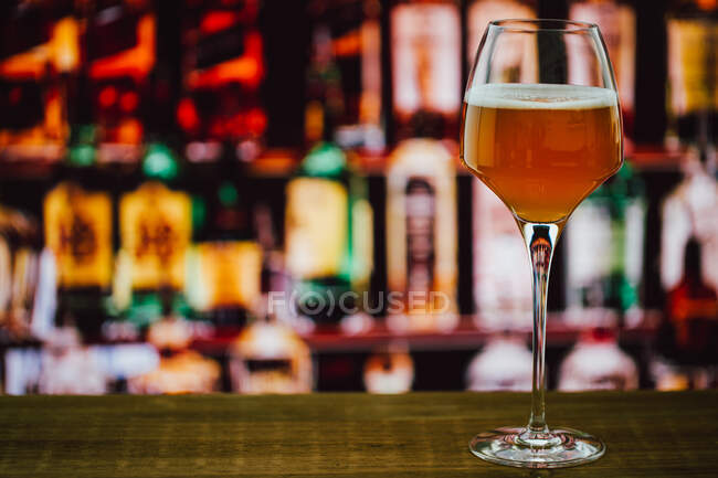 Beer in wineglass with foam in glass on wooden counter in bar on blur background — Stock Photo