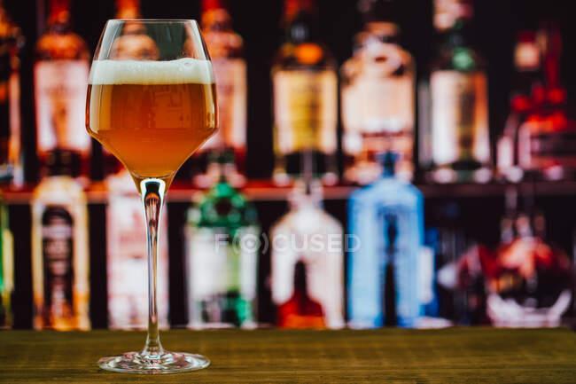 Bier im Weinglas mit Schaumstoff im Glas auf Holztheke in Bar auf unscharfem Hintergrund — Stockfoto