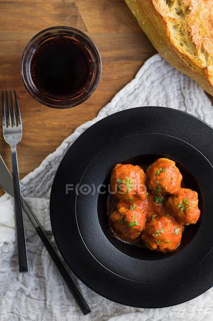 Сверху вкусные вареные фрикадельки с томатным соусом, подаваемые с хлебом на черной тарелке с котлетами и напитками на столе — стоковое фото