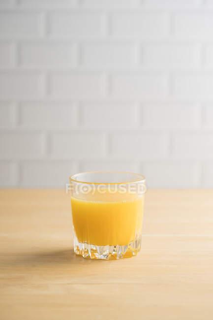 Zumo de naranja en vaso sobre la mesa - foto de stock
