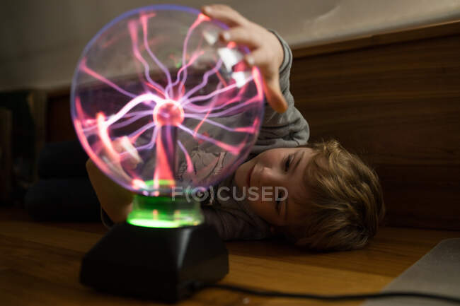 Boy looking at mysterious glass lightening lamp on table — Stock Photo