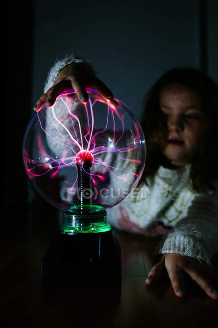 Transparent glass electrical round lamp under hand of adorable girl in dark — Stock Photo