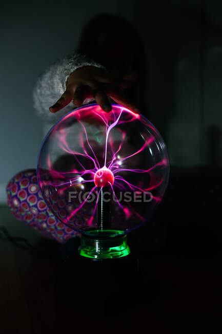 Charmed girl touches glowing ball with hand in dark — Stock Photo
